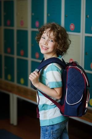 beginning school year: Elementary school student standing near lockers in school hallway. Behind kids school backpack. The boy has blond curly hair and blue eyes. HE smiles. Stock Photo