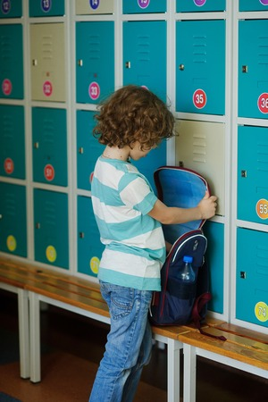 Little learner standing in the hall near the lockers and searching for something in his backpack. The boy stands with his back to the camera. Have curly blond hair
