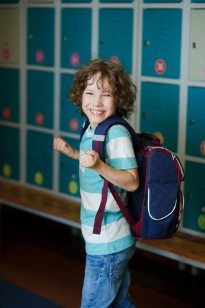 Elementary school student standing near lockers in school hallway. Behind kids school backpack. Stock Photo