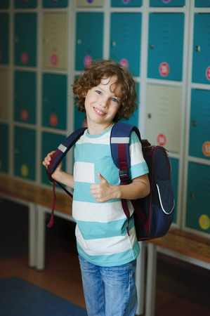 Elementary school student standing near lockers in school hallway. Behind kids school backpack. The boy has blond curly hair and blue eyes. With a gesture he showed that hes all right.