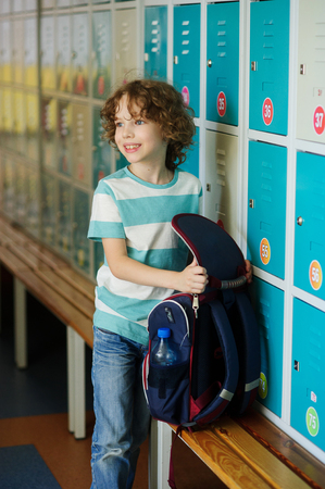first year student: Little learner standing near lockers in school hallway. He put the backpack on the bench and retrieved something from it. The boy somewhere looks.