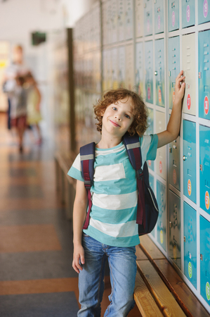learner: Little learner standing near lockers in school hallway. He put his hand on my locker. The boy with a wistful smile, looking at the camera. Stock Photo