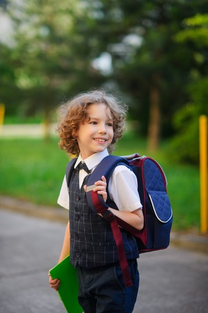 smartly: A first grader goes to school. Little schoolboy standing in the school yard the yard. Elementary school student is smartly dressed. Behind the boys school backpack. Back to school.