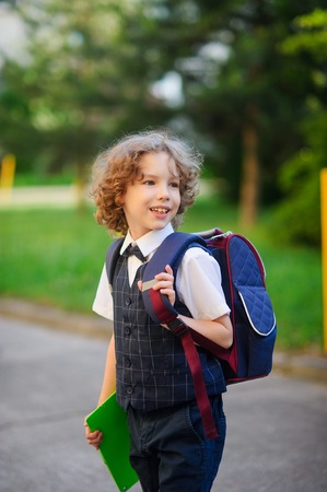 smartly: Little schoolboy standing in the school yard. Elementary school student is smartly dressed. Behind the boys school backpack. The first grader looks away and smiles. Back to school.