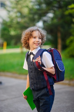 grader: Little schoolboy standing in the school yard. Elementary school student is smartly dressed. Behind the boys school backpack. The first grader looks away. Back to school. Stock Photo