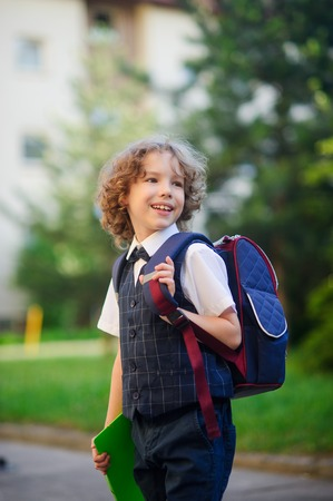 grader: The primary school students standing in the school yard. Little schoolboy smartly dressed. Behind the boys school backpack. The first grader looks away and smiles. Back to school. Stock Photo