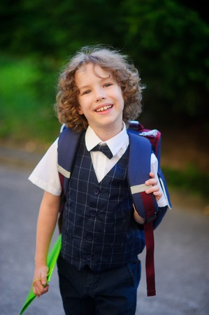smartly: Cute little first grader goes to school. The primary school students smartly dressed. Behind the boys school backpack in his hands - bright folder. The student looks at camera and smiling. Back to school. Stock Photo