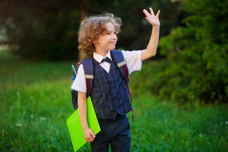 smartly: Curly blond student goes to school. The primary school students smartly dressed. Behind the boys school backpack in his hands - bright folder. Schoolboy looks to the side and someone waving his hand.