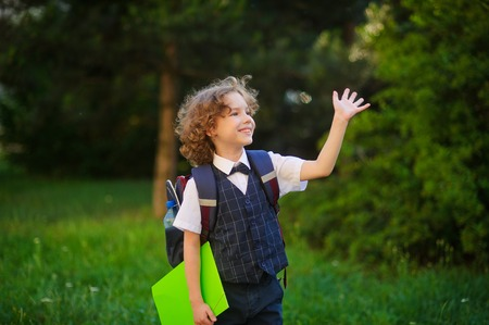 smartly: Curly blonde first-grader goes to school. The primary school students smartly dressed. Behind the boys school backpack. The schoolboy looks to the side and someone waving his hand. Back to school.