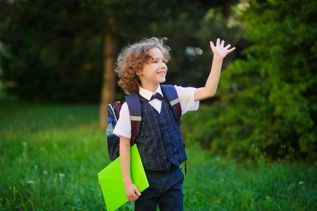 first year student: Blonde first-grader goes to school. The primary school students smartly dressed. Behind the boys school backpack in his hands - bright folder. Schoolboy looks to the side and someone waving his hand. Stock Photo