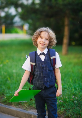 smartly: Little schoolboy standing in the school yard. The student is smartly dressed. He looks at the camera with a sweet smile. Behind the boys backpack. On the background of lush greenery. Back to school.