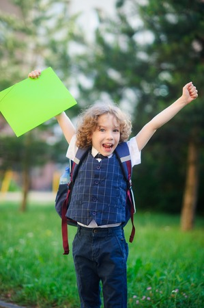 Little schoolboy rejoices. The boy raised up both hands. The student is smartly dressed. He looks at the camera with a smile. Behind the boys backpack. Back to school.