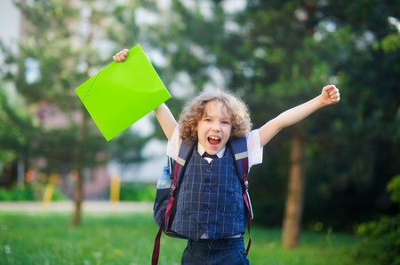 beginning school year: Little schoolboy angry. The boy raised up both hands. The student is smartly dressed. He looks into the camera with an angry expression. Behind the boys backpack. Back to school. Stock Photo