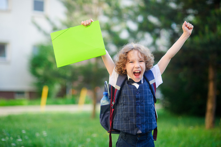 smartly: Little schoolboy angry. The boy lifted up both hands and clenched his fists. The student is smartly dressed. He looks into the camera with an angry expression. He opened his mouth. Back to school. Stock Photo