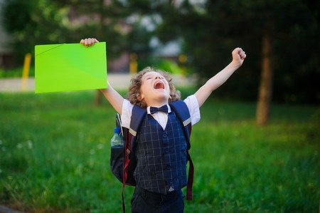 The little first grader is very angry. The student raised both hands and clenched his fists. He looked up to the sky with an angry expression. He opened his mouth. In hand the boy has a bright folder. Stock Photo