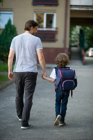 The father leads by the hand his son to school. A tall man and a little schoolboy. Behind the boys backpack. The view from the back. Back to school.