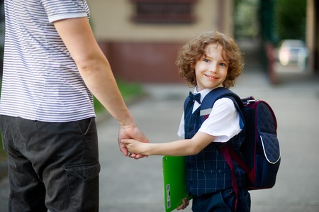first year student: Cute little first grader goes to school. He held his fathers hand. The boy turned around and smiled. Behind the schoolboys backpack. He is smartly dressed. Back to school Stock Photo