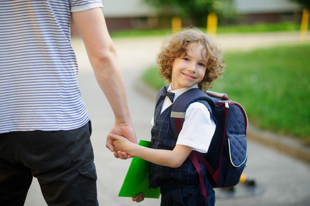beginning school year: Cute little elementary school student goes to school. He held his fathers hand. The boy turned around and smiled. Behind the schoolboys backpack. He is smartly dressed. Back to school