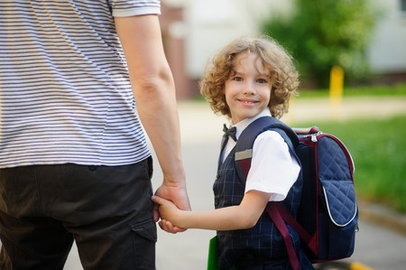 schoolboys: Cute little student goes to school. He clings to the hand of the father. The boy turned around and smiled. Behind the schoolboys backpack. He is smartly dressed. Back to school