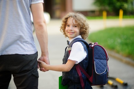 Cute little first grader student going to school with dad. He clings to the hand of the father. The boy turned around and smiled. Behind the schoolboys backpack. He is smartly dressed. Back to school