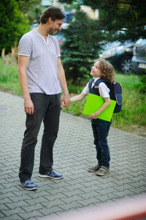 smartly: Cute little first grader is with his father in the school yard. They lovingly look at each other. Father keep his sons hand. Behind the schoolboys backpack.The boy is smartly dressed. Back to school