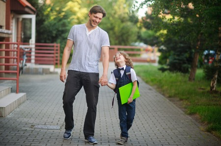 disciple: Father escorted to school by his son. The tall man tightly holding the hand of small disciple. Father and son with love and tenderness look at each other and something fun to talk. Back to school