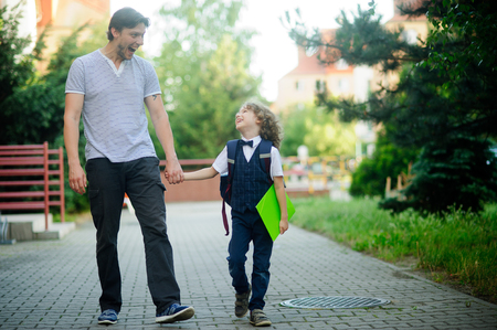 schoolboys: Cute little first grader is going with his father to school. The Pope amused the boy to cheer him up. Father keep his sons hand. Behind the schoolboys backpack. The boy is smartly dressed. B
