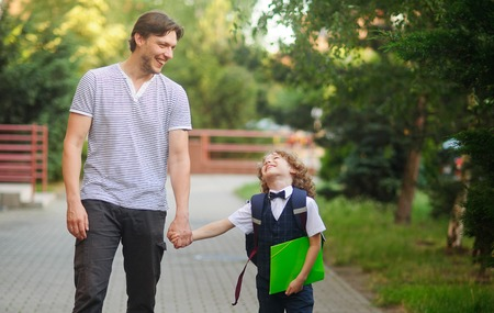 Dad escorted to school by his son. The tall man tightly holding the hand of small disciple. Father and son with love and tenderness look at each other and something fun to talk. A first grader is smartly dressed. Back to school Stock Photo
