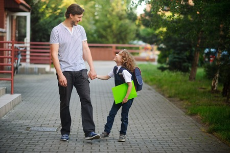 smartly: Dad walks to school his son. The tall man holds the hand of a little schoolboy. Father and son with love and tenderness look at each other. The boy is smartly dressed. Back to school Stock Photo