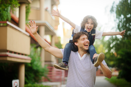 First grader sitting on the shoulders of his father. He is very happy. Father and son pretending to fly. They have a good mood. Stock Photo