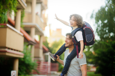 Little pupil sitting on the shoulders of his father. He placed his hands to the sides as if flying. Dad and son a great mood. They play on the way to school. Behind the schoolboys backpack.