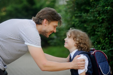 solicitude: The father sees off in school of the son-first-grader. It has bent to the boy and has taken it for shoulders. The father and the son look against each other with love and smile.