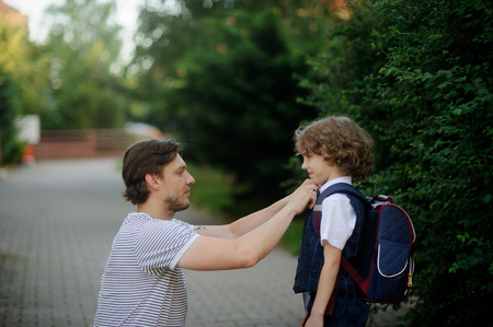 solicitude: The father sees off the son-first-grader in school. It has sat down near to the boy and carefully corrects for its clothes. The boy looks at the daddy with love and smiles.
