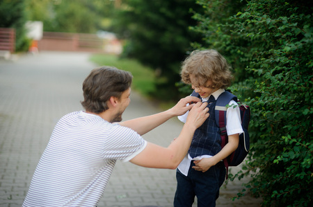 he laughs: The father accompanies his son-grader to school. He sat down next to the boy and carefully straightens his clothes. A boy looks at dad and happy laughs.