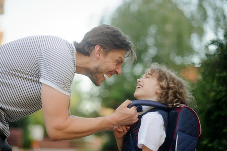 disciple: The father sees off the son-student in school. It carefully corrects for a backpack of the boy and does the ridiculous person. The small disciple looks at the daddy and laughs.
