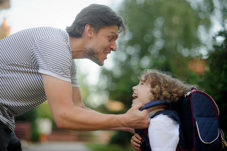 he laughs: The father sees off the son-first-grader in school. He amused the boy to cheer him. Little schoolboy looks at dad and laughs.