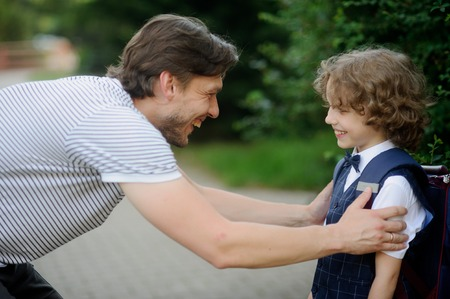 solicitude: The father sees off the son-schoolboy in school. It has bent to the boy and has taken it for shoulders. The father and the son look against each other with love and smile. Stock Photo