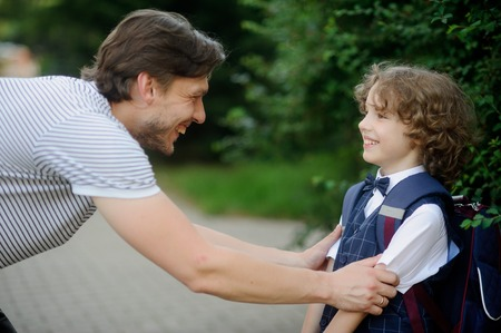 The father sees his son first-grader at the school. He leaned over to the boy and took him by the shoulders. Father and son look at each other with love and smile.