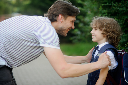 solicitude: Father with his son-first-graders in the school yard. It has bent to the boy and has taken it for shoulders. The father and the son look against each other with love and smile.