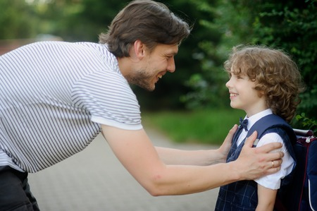 beginning school year: Father with his son-first-graders in the school yard. It has bent to the boy and has taken it for shoulders. The father and the son look against each other with love and smile.