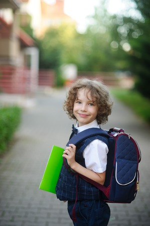 kinky: Little Kinky schoolboy stands in the courtyard of the school. The boys cute face. Behind the backpack, in the hands of bright green folder. Boy looks into the camera and smiles.