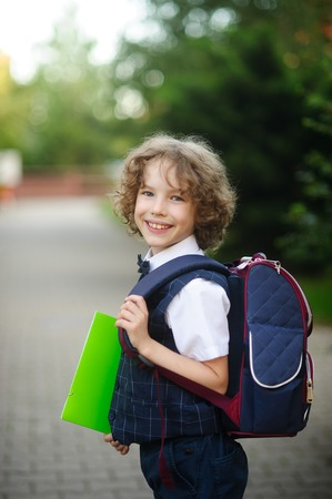 scholastic: Little curly grader stands in the school yard. The boys sweet face. Behind backpack in hands - bright green folder. Schoolboy looks into the camera and smiling.