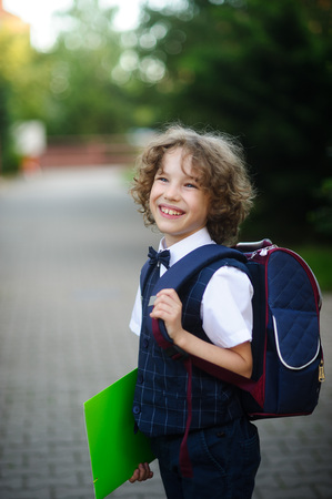 disciple: Cute little schoolboy standing on the sidewalk. It is elegantly dressed. Behind the boy a school backpack. The disciple holds a bright folder in a hand and smiles. Stock Photo