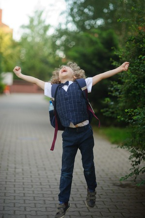 Little schoolboy as if flying. The boy spread his arms, his face raised to the sky. Stock Photo