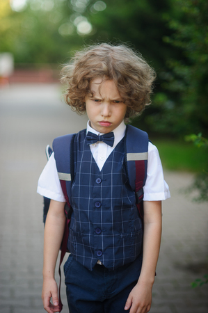 Little schoolboy stands in the school yard with an angry expression on his face. Boy bend ones brows. Curly hair tousled . He does not want to go to school . Stock Photo
