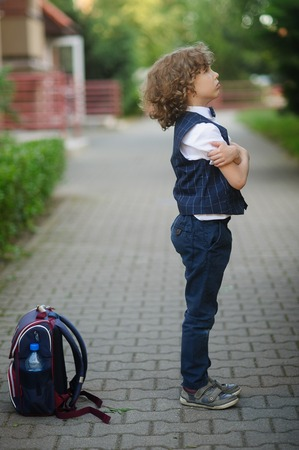 Little schoolboy stands in the school yard with an angry expression on his face . The boy crossed his arms . Students backpack lying on the ground nearby. He does not want to go to school . Side view