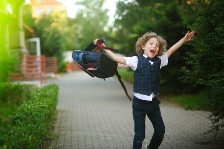 niño con mochila: El colegial se balancea con rabia su mochila en el patio de la escuela. pelo rubio rizado, la boca abierta. El niño que no quería volver a la escuela. Estrés.