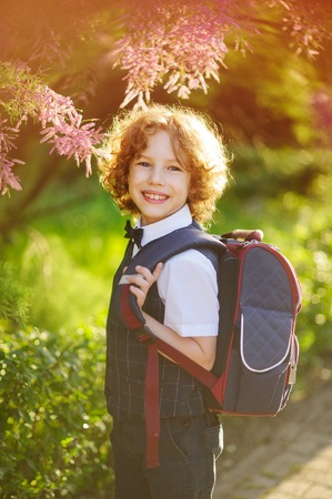 The first grader standing about beautifully blossoming bush. Sunny day. Little schoolboy smiling looking at the camera. The boy has blond curly hair and blue eyes. Behind the student school backpack. Stock Photo