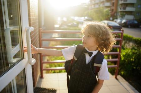 lad: Little pupil in school uniform opens the door. Cute blonde lad. Behind him a school backpack. The apprentice is back from school.