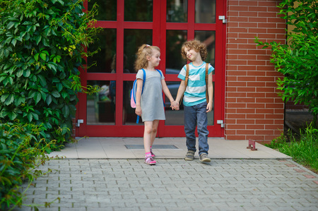 Little school students go on a schoolyard holding hands. Children with a smile look at each other. Boy and girl. Schoolmates. Stock Photo